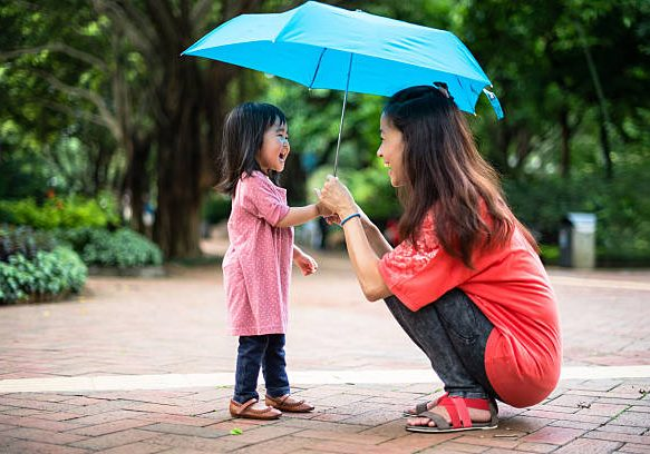 Young mom holding a blue umbrella with toddler girl together, both looking at each other smiling cheerfully, and having fun playing with the umbrella in the park.